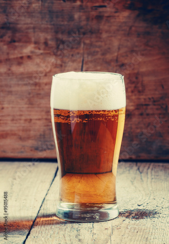 large glass of light beer with foam on the old wooden background Poster