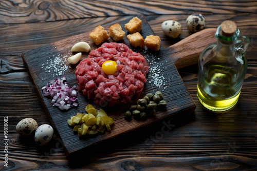 Photo  Beef tartare with egg yolk, capers, sliced pickles and onion