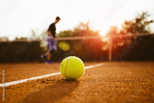 Photo  Tennis ball and silhouette of player on a clay court
