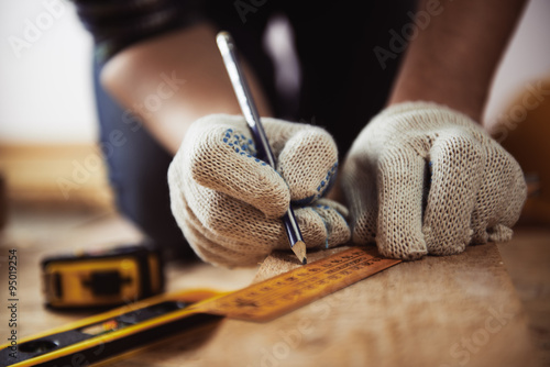 Obraz Close-up of craftsman hands in protective gloves measuring wooden plank with ruler and pencil. Woodwork and renovation concept.  - fototapety do salonu