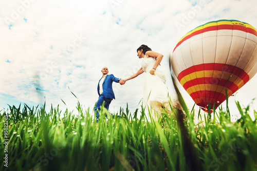 Photo bald groom and brunette bride on background balloon and cloudy s