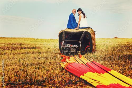 Photo bald groom and brunette bride look at camera sits on basket of b
