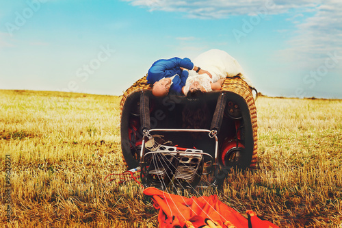 bald groom and brunette bride look at camera lying on basket of Wallpaper Mural
