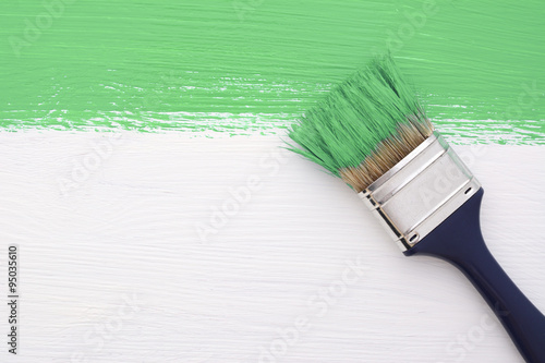 Stripe of green paint with a paintbrush on white
