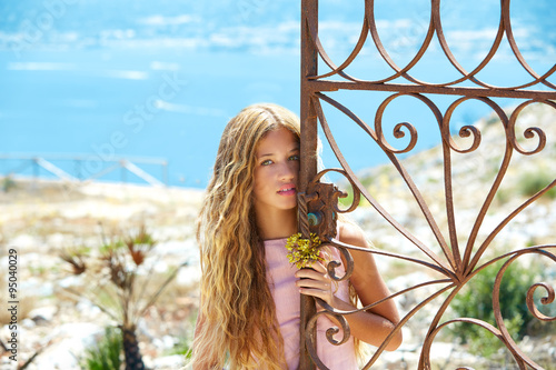 Fotografía  Blond girl in Mediterranean rusted gate at sea