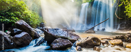 Aluminium Prints Waterfalls Tropical waterfall in jungle with sun rays