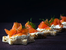 Row Of Festive Canapes In Star Shape With Smoked Salmon On Dark