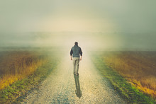 Man Walking To The Light On A Dirt Road