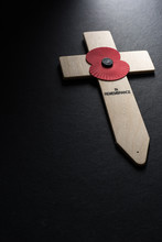 Remembrance Day Poppy Symbol On Wooden Cross, Background