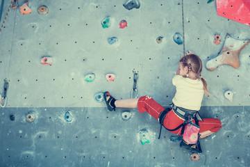 Fototapeta little girl climbing a rock wall