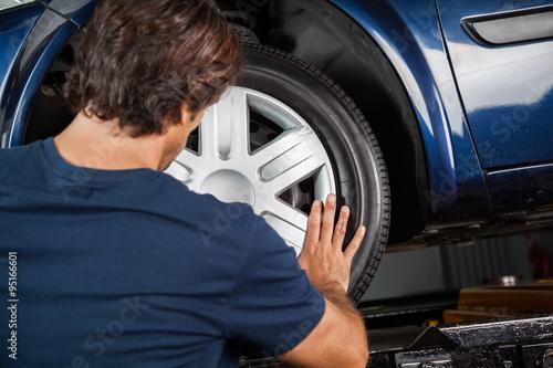 Fotografie, Obraz  Mechanic Fixing Hubcap To Car Tire