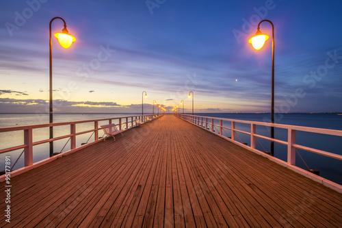 drewniane-molo-nad-morzem-oswietlone-przez-stylowe-lampy-w-nocy