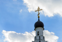 Cross On The Dome Of  The Church Against The Blue Sky