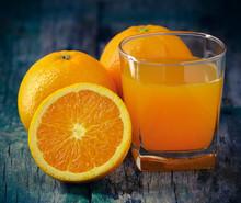 Orange Juice Glass And Fresh Oranges On Wood