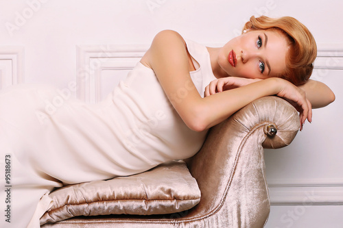 young woman with blond hair in retro style,wears elegant white dress