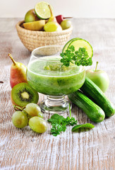 Fototapeta Refreshing green detox smoothie with ingredients on wooden background, selective focus