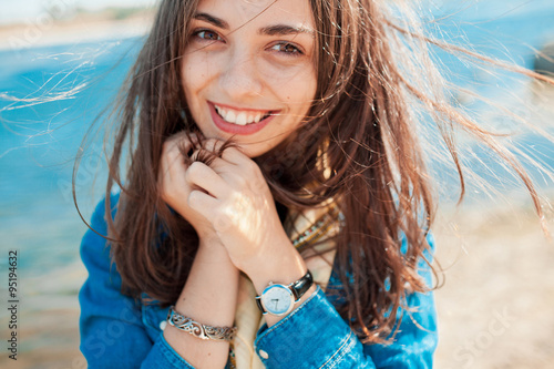 fototapeta na lodówkę Beautiful sunny portrait of a shy girl looking at the camera with lake background. Teenage girl holding hands at face because of modesty