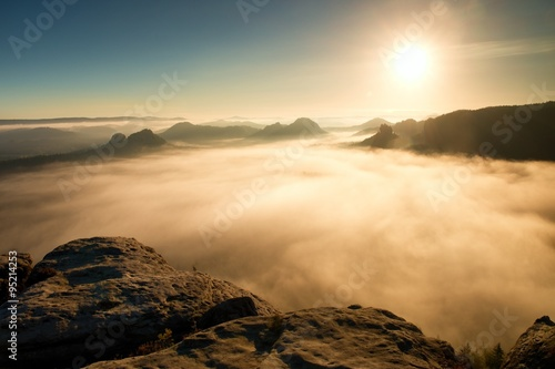 Poster Marron chocolat Autumn colorful morning in rocky park. View into long deep valley full of heavy colorful mist. Autumn landscape after rainy night
