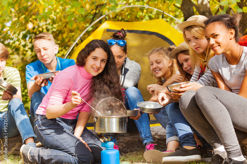 Obraz Teenagers cook soup in metallic pot during camping - fototapety do salonu