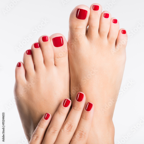 Poster Pedicure Closeup photo of a female feet with beautiful red pedicure