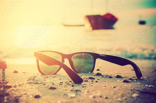 black sunglasses and sea background with blure boat