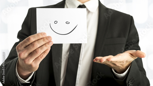 Fotografía  Man in elegant business suit holding up a white card with smiley