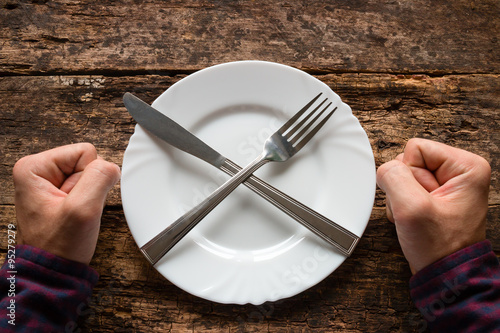 man refuses to eat spoon and fork on a plate stacked in the shape of a cross Canvas-taulu