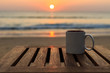 canvas print picture - Coffee cup on wood table at sunset or sunrise beach