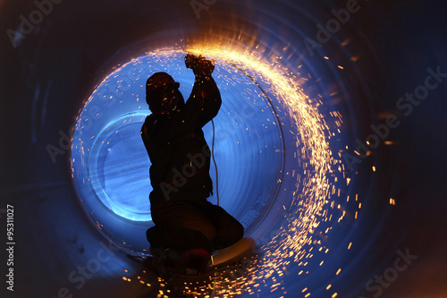 Fototapeta A worker works inside a pipe on a pipeline construction obraz