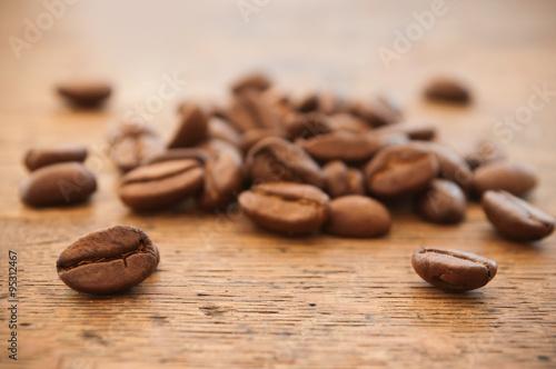 Poster Koffiebonen grains de café en gros plan sur table en vieux bois