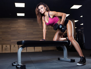 Fototapeta Fitness / Siłownia Fitness young sexy girl in the gym doing exercises with dumbbell