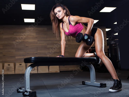 Fitness young sexy girl in the gym doing exercises with dumbbell - 95317468