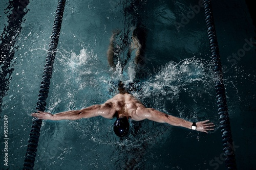 Obraz na płótnie Sportsman swims in a swimming pool