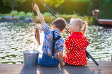 Little Boy And Girl Fishing In A River. Sitting On A Wood Pontoon