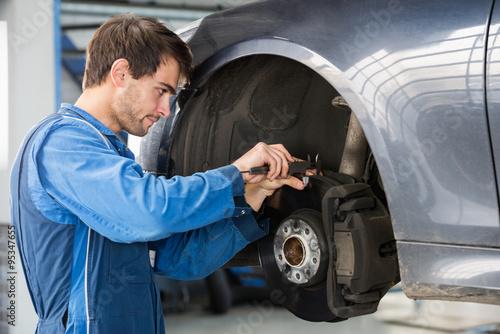 Photo  Car Mechanic Examining Brake Disc With Caliper