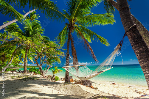 Fotobehang Strand Empty hammock in the shade of palm trees on tropical Fiji