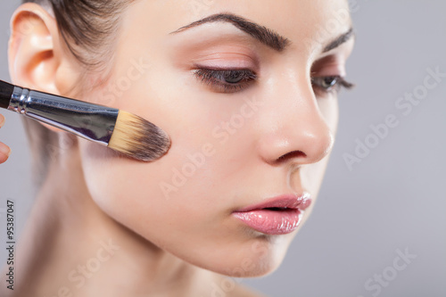 af2059f72 Beauty girl with makeup brushes. Perfect smooth skin.Applying makeup ...