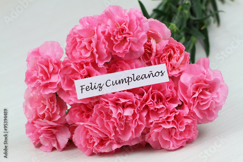 Feliz Cumpleanos Happy Birthday In Spanish Card With Pink Carnations On Rustic Surface