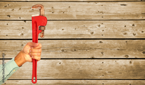 Papiers peints Bois Hand of plumber with a wrench.