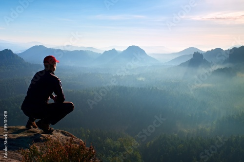 Poster Gris Runner in red cap and in dark sportswear in squatting position enjoy mountain scenery