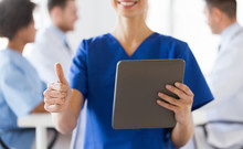 Close Up Of Nurse With Tablet Pc Showing Thumbs