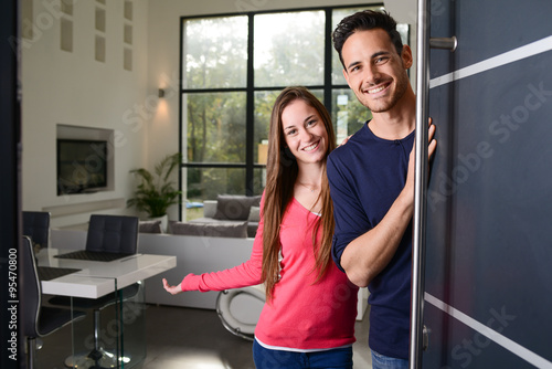 Slika na platnu happy young couple at new house front door welcoming people