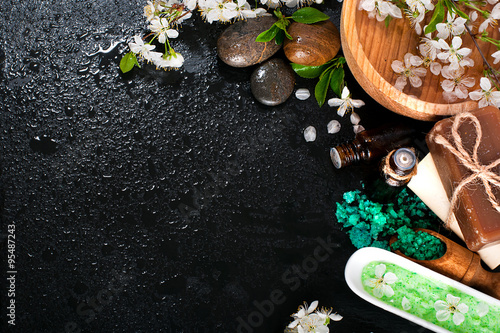Poster de jardin Spa Spa concept on a dark background. Sea salt, flowering branches of cherry, aromatic oils