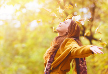 Beautiful Young Woman Throwing Leaves In A Park, Enjoying