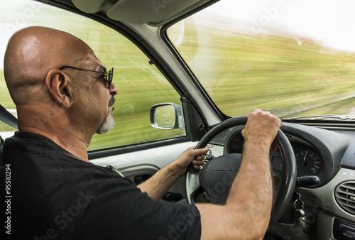 Hombre calvo viaja en su furgoneta a gran velocidad. Fototapet