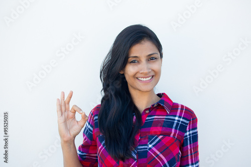 Fotografie, Obraz  Closeup portrait of young happy, smiling excited beautiful natural woman in plaid red shirt giving OK sign with fingers, isolated white wall background
