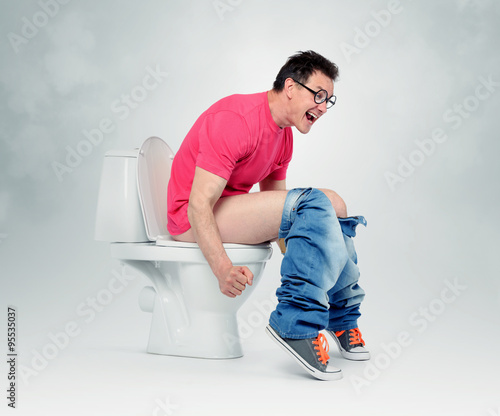 Valokuva  Man with glasses straining on the toilet