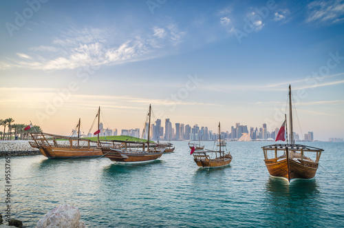 Fotografie, Obraz  Dhows moored off Museum Park in central Doha, Qatar, Arabia, with some of the buildings from the city's commercial port in the background