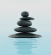 Stack of black zen stones in water.