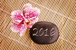 2016 written on a black pebble with pink orchid, zen greeting card